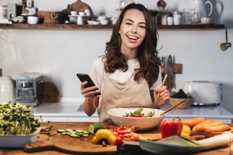 woman cooking with phone