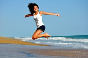 woman jumping in sand