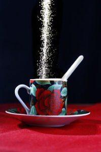white table sugar flowing into mug