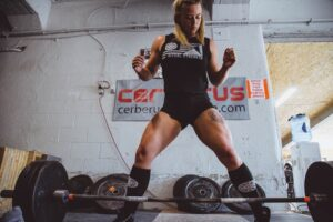muscly woman lifting barbell